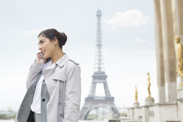 woman on phone in front of Eiffel Tower