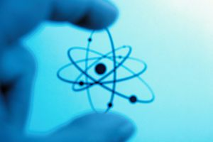 Fingers zeroing in on a depiction of an atom