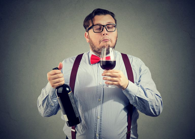 A snooty sommelier in a bowtie and horn-rimmed glasses smells a glass of wine
