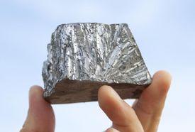 Hand holding pure zinc metal