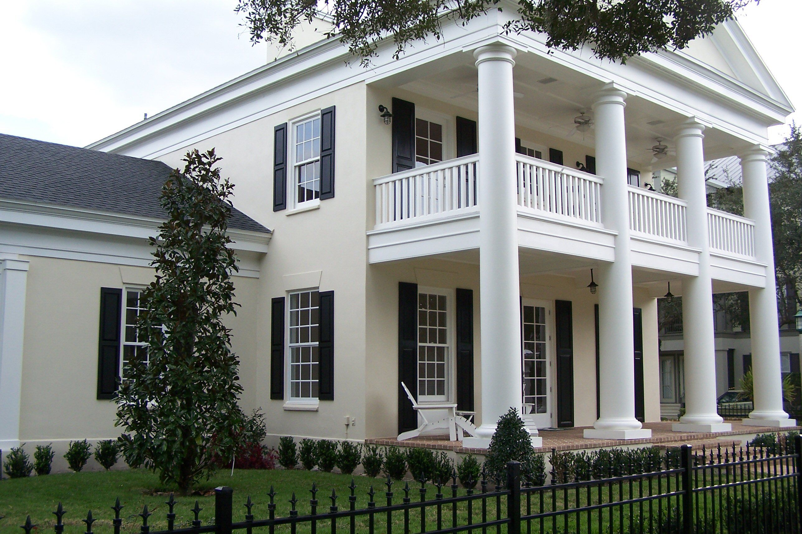 house with 4 massive columns, two-story front porches, and a large pediment