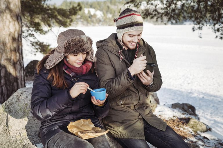 Couple having food while sitting on rock at field during winter