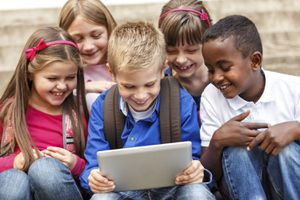 A group of children huddled around a tablet