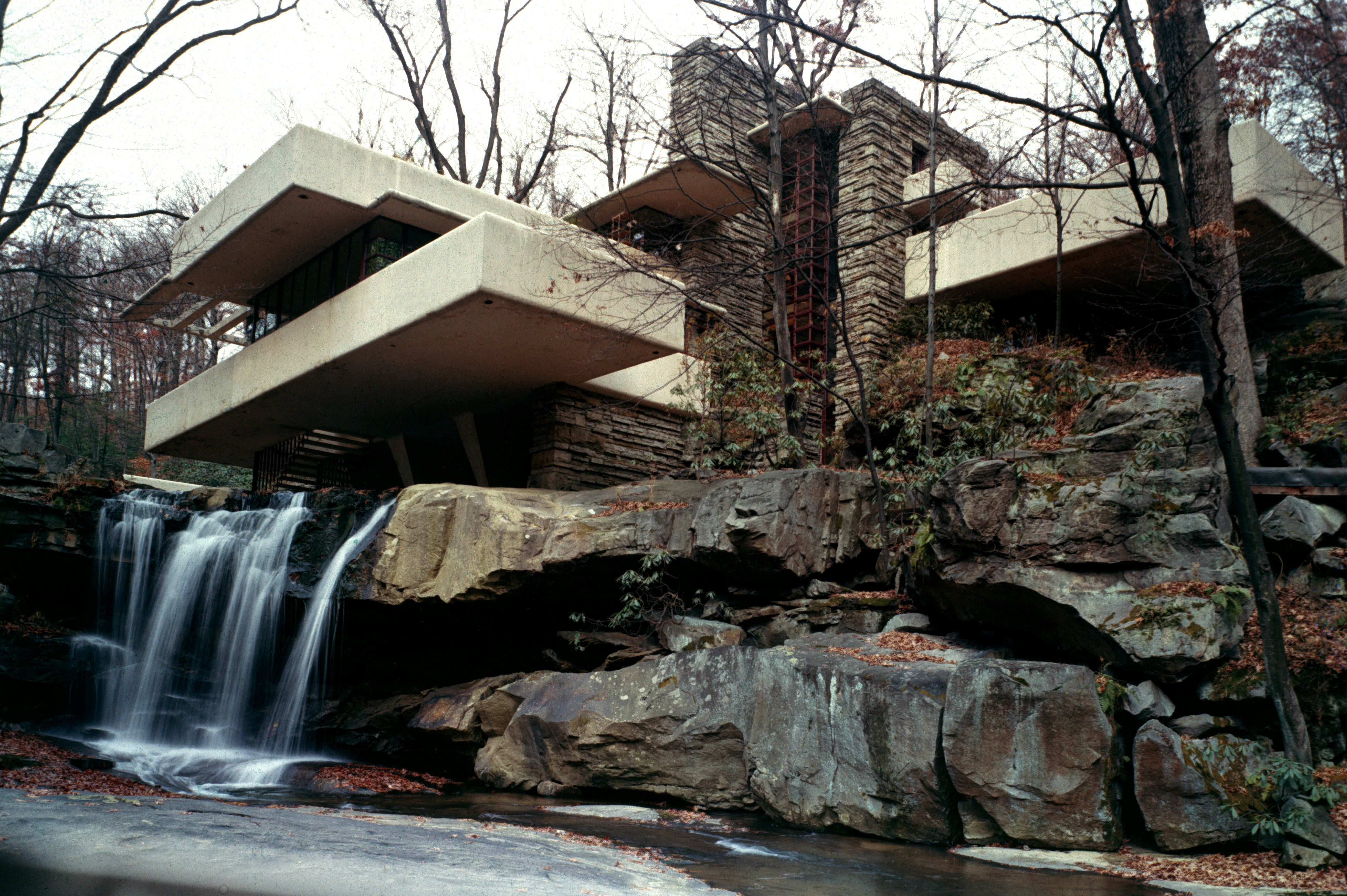 modern house with many cantilevered levels built into the side of a hill near a creek, with water running underneath the house into the water below