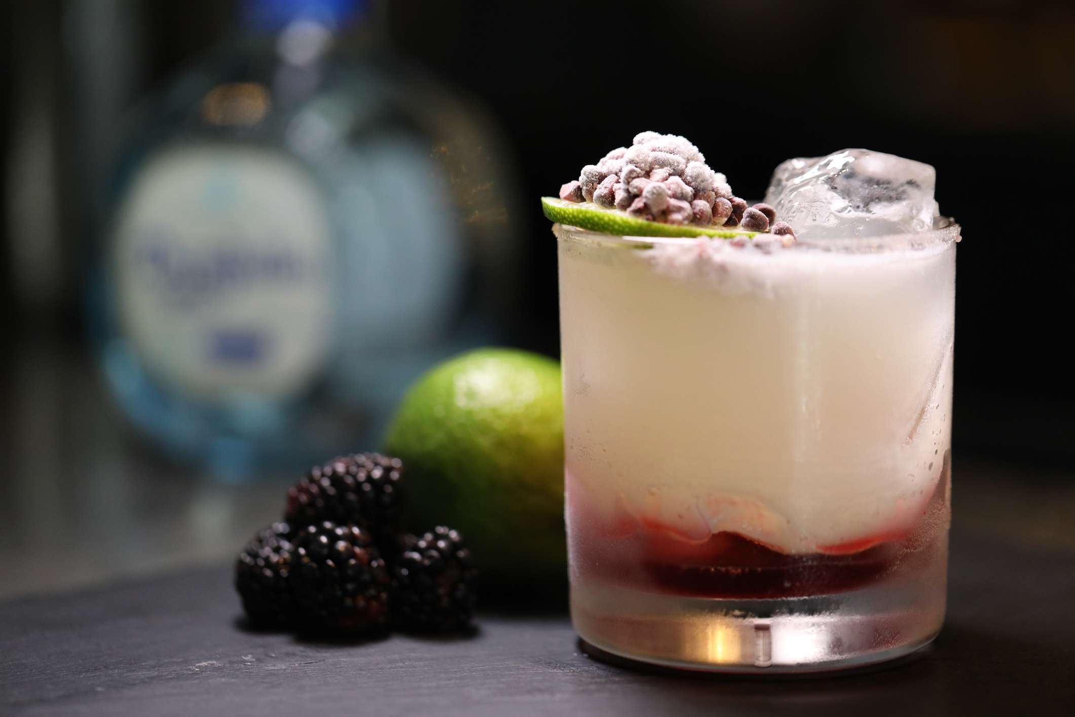 A blackberry and lime tequila cocktail poured over ice and garnished with dry ice