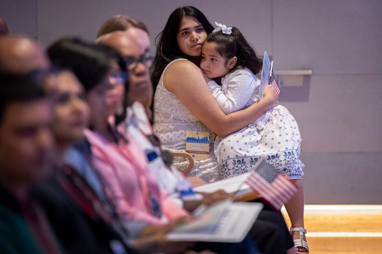 Carmen del Thalia Mallol holds her daughter Lia, 4, as she waits to take the Oath of Allegiance during a naturalization ceremony inside the National September 11 Memorial Museum on July 2, 2019 in New York City.