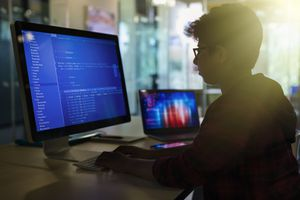 Boy student programming at computer in dark classroom