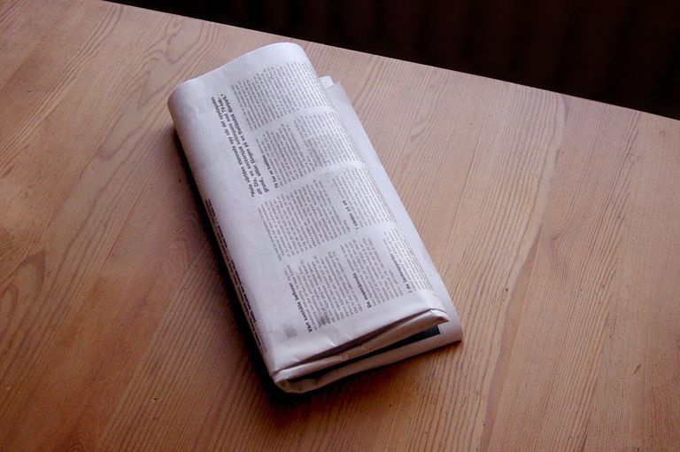 A folded newspaper on a table.