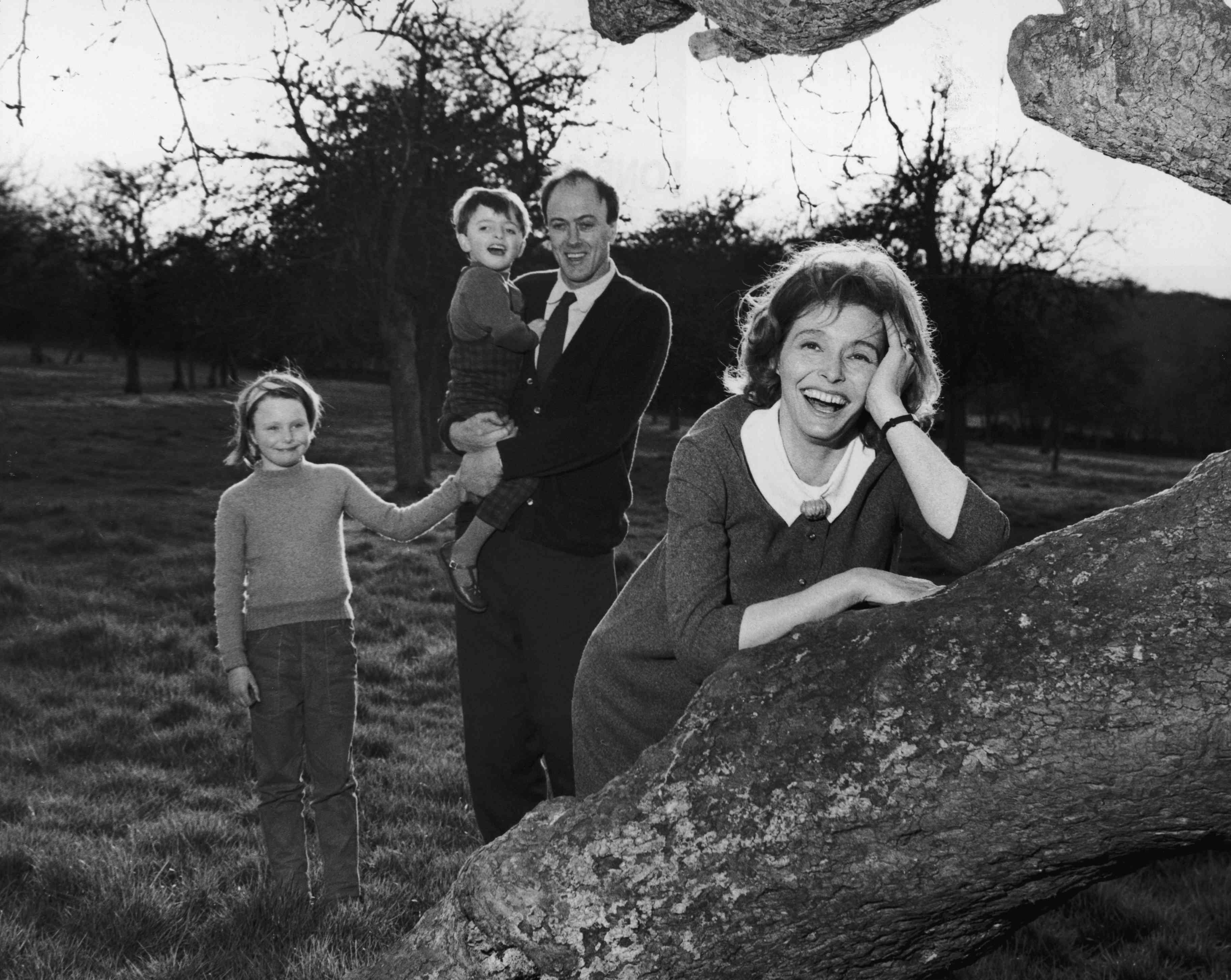 Fotografía en blanco y negro de Roald Dahl sosteniendo a sus hijos;  su esposa Patricia Neal se apoya en un árbol