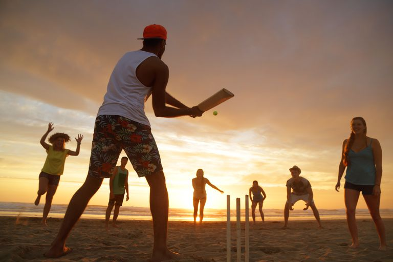 Group of young people playing cricket on beach at sunset.