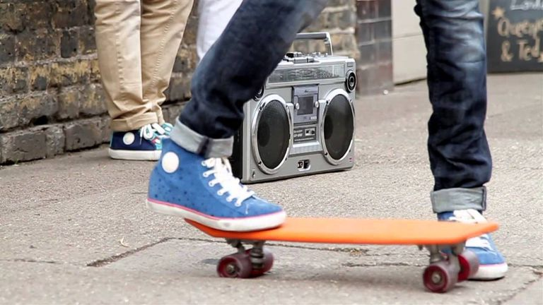Kid in jeans riding a skateboard