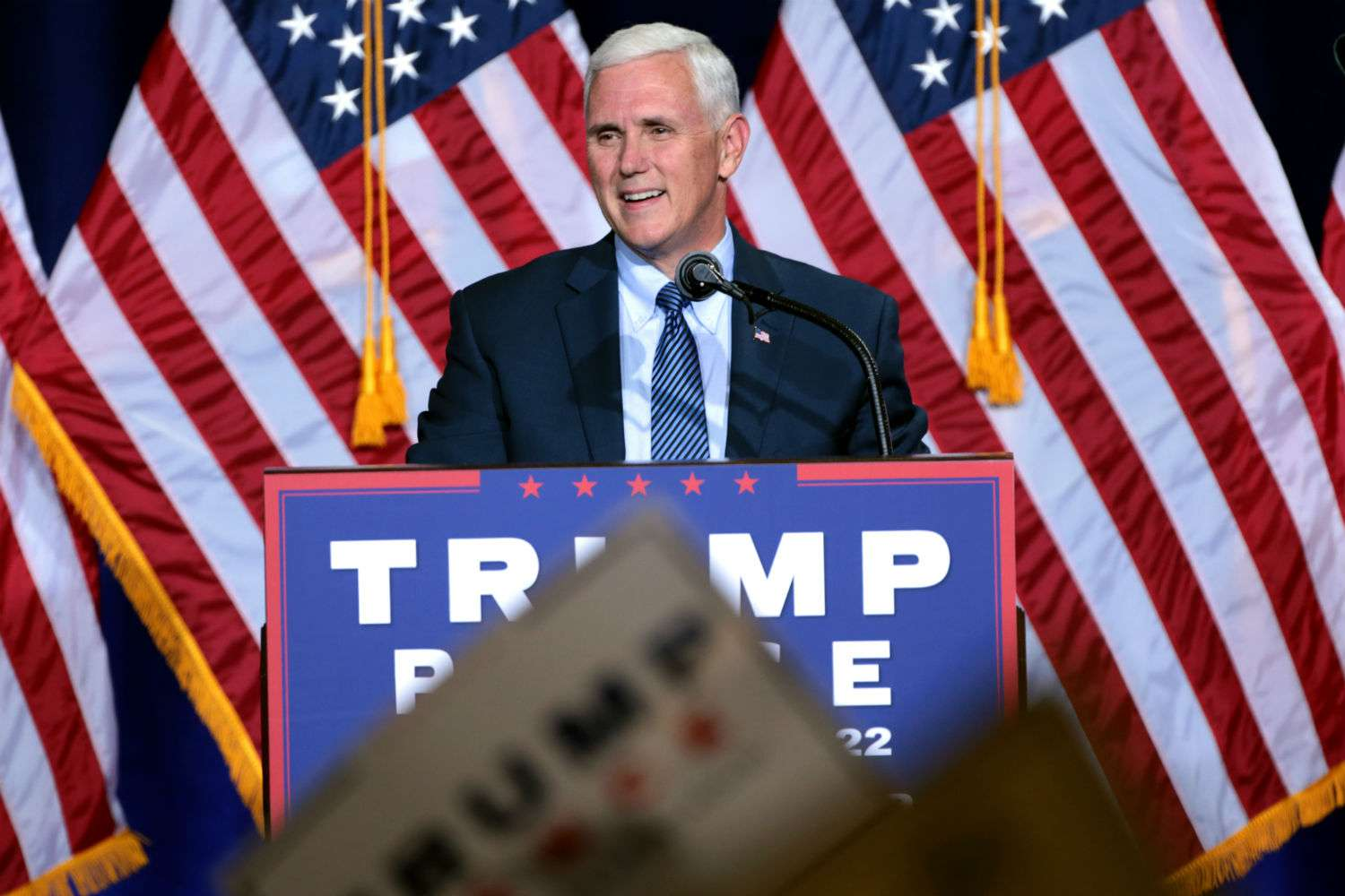 Pence speaks at a rally with American flags behind him.
