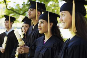 Group of graduates with diplomas on university campus (differential focus)