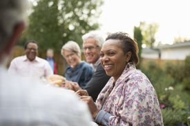 Smiling woman enjoying a garden party with friends