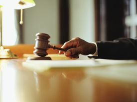 Male judge striking gavel in courtroom, close-up