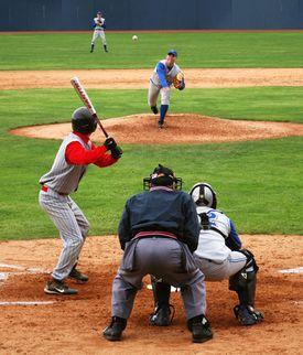 Pitcher pitching baseball to batter.