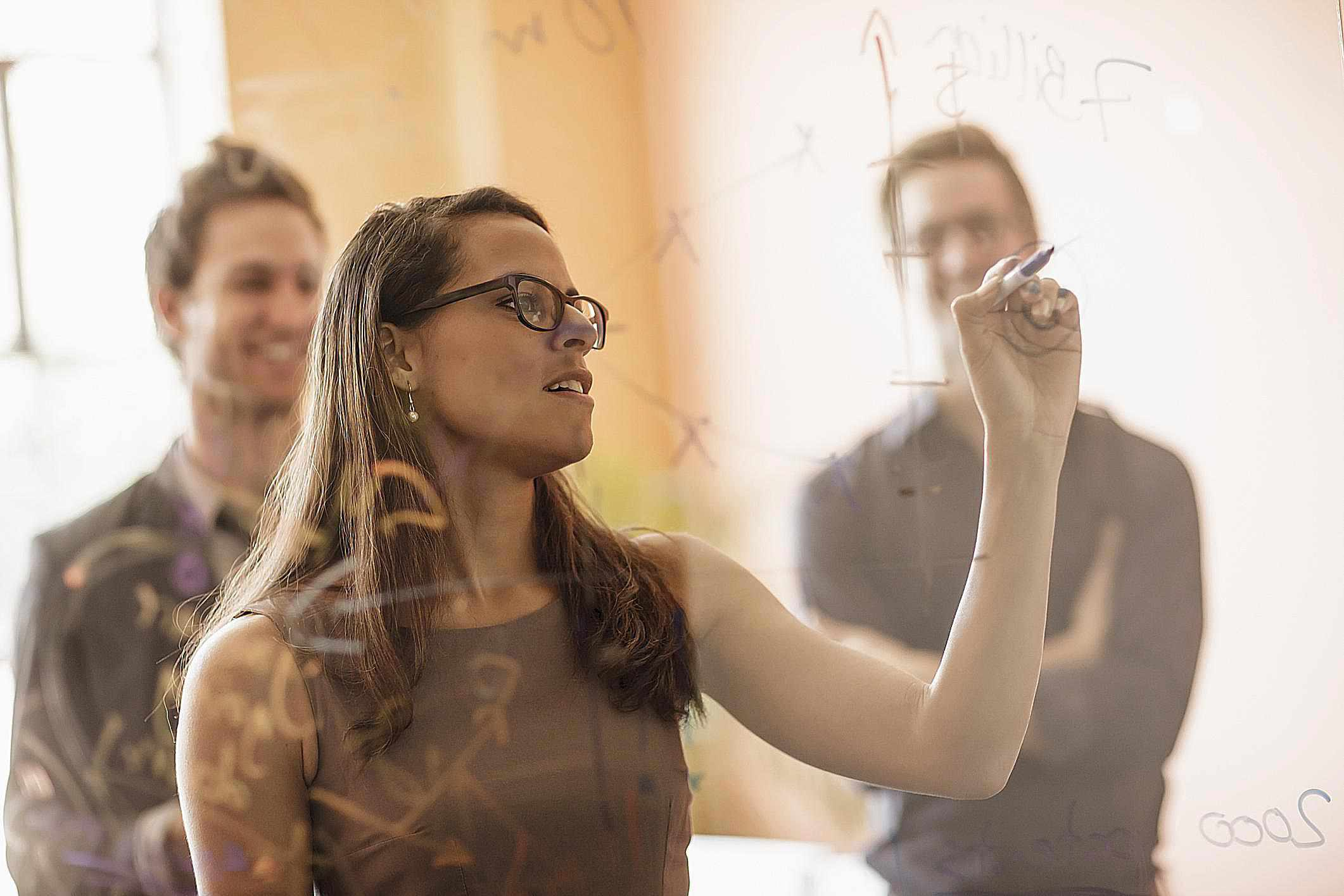 Businesswoman writing on wall while coworkers watch