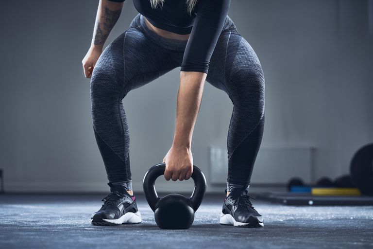 Close-up of athletic woman exercising with kettlebell at gym