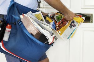 A mailman stuffing junk mail into a mailbox
