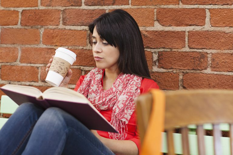 Woman reading book and drinking coffee