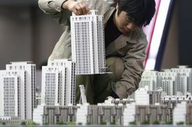 A worker installs a building model during the Beijing Winter Real Estate Fair