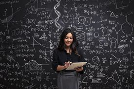 Woman on a tablet with math chalkboard