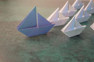 Origami paper sailboats, leadership business concept, toning