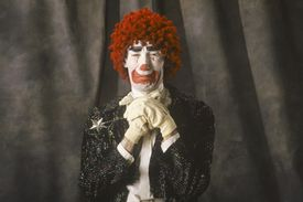 A sad clown posing with hands folded