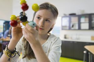A girl studies a model of a molecule in a classroom
