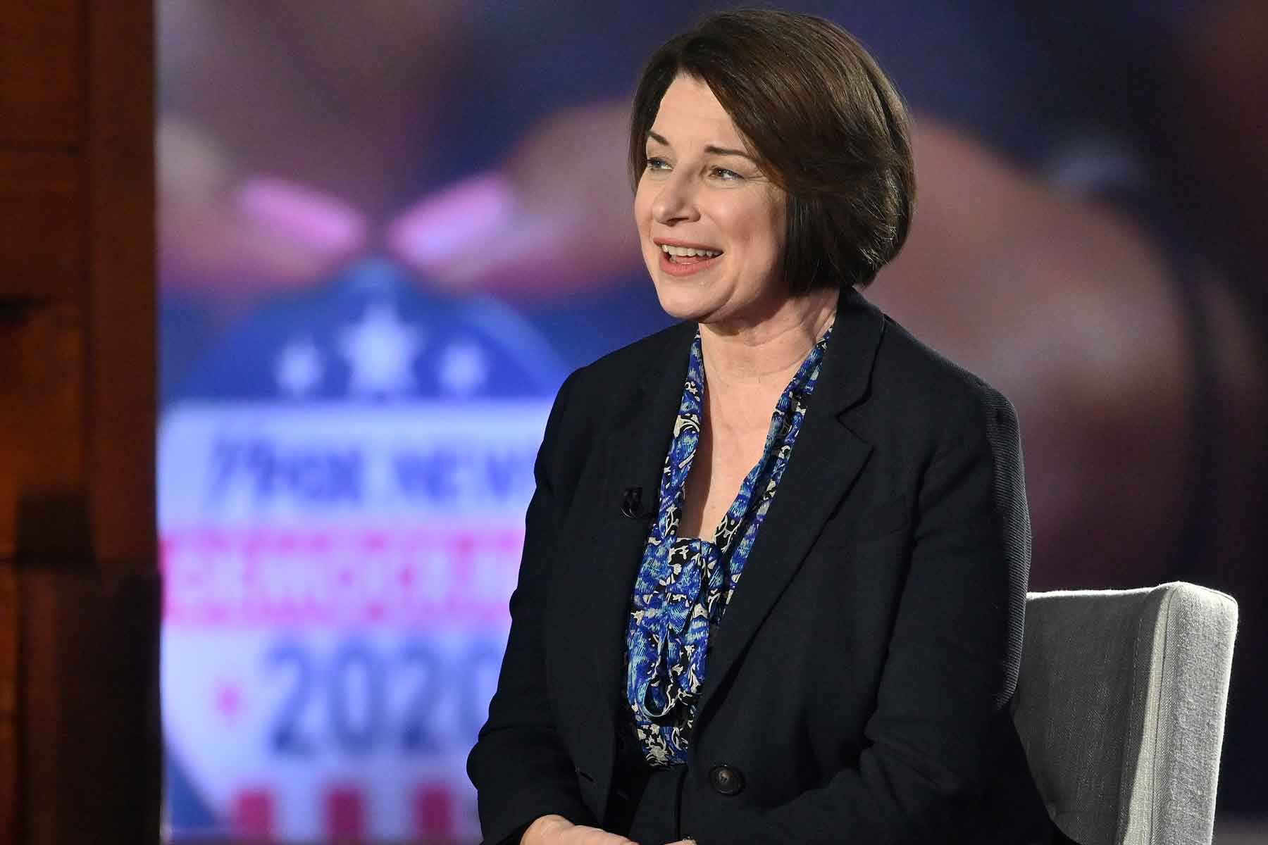 amy klobuchar sits with her hands folded