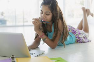 preteen lying on floor with laptop and homework