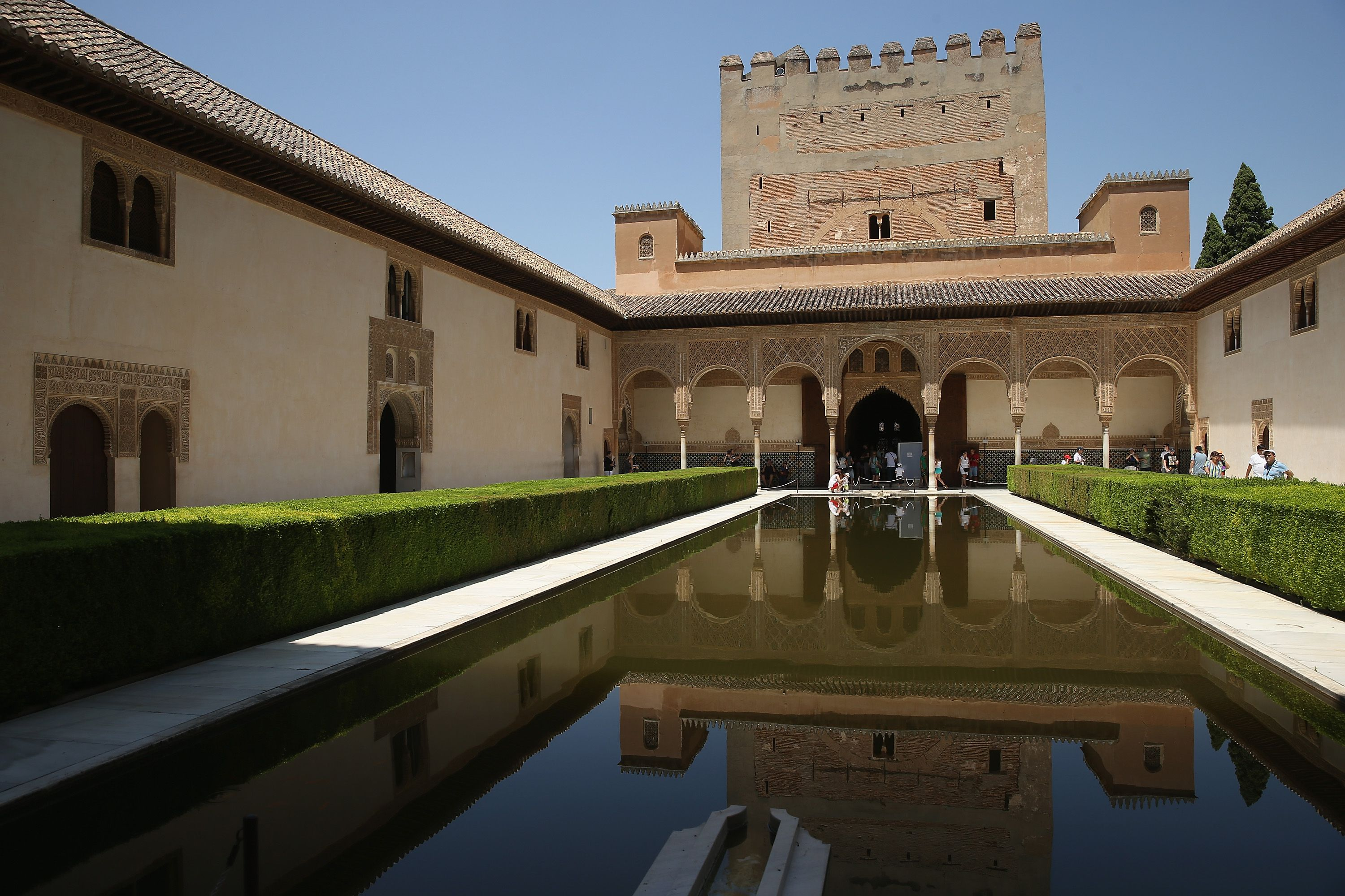 a courtyard of pathways and hedges surrounding a reflecting pool