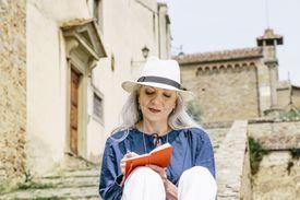 Stylish mature woman writing in notebook outside church, Fiesole, Tuscany, Italy