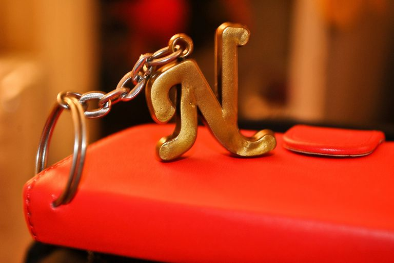"Capital ""N"" key ring attached to a red book close up."
