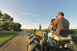 A man and child riding a tractor with farmland stretched out around them on a sunny day.