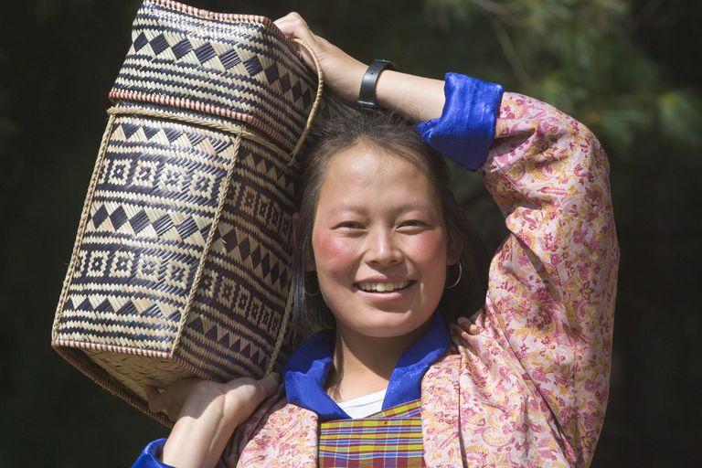Happy woman carrying a basket in Bhutan