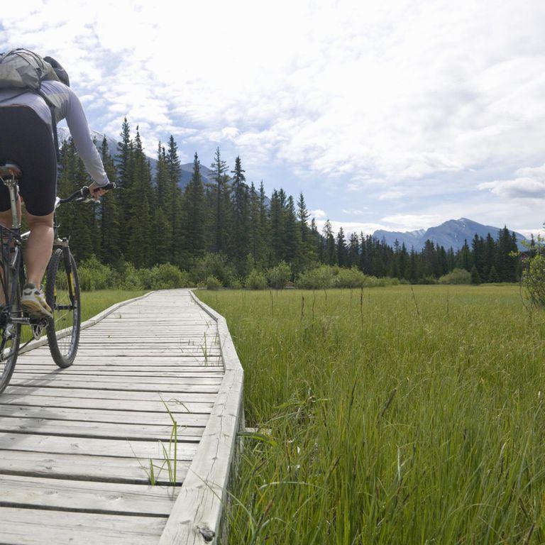 Woman mountain biking along mountain boardwalk