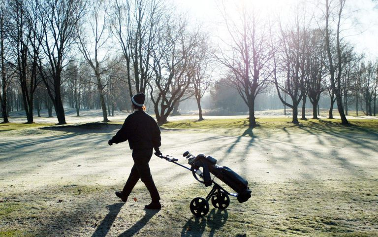 Golfer pulling golf clubs on pull cart on golf course in Winter