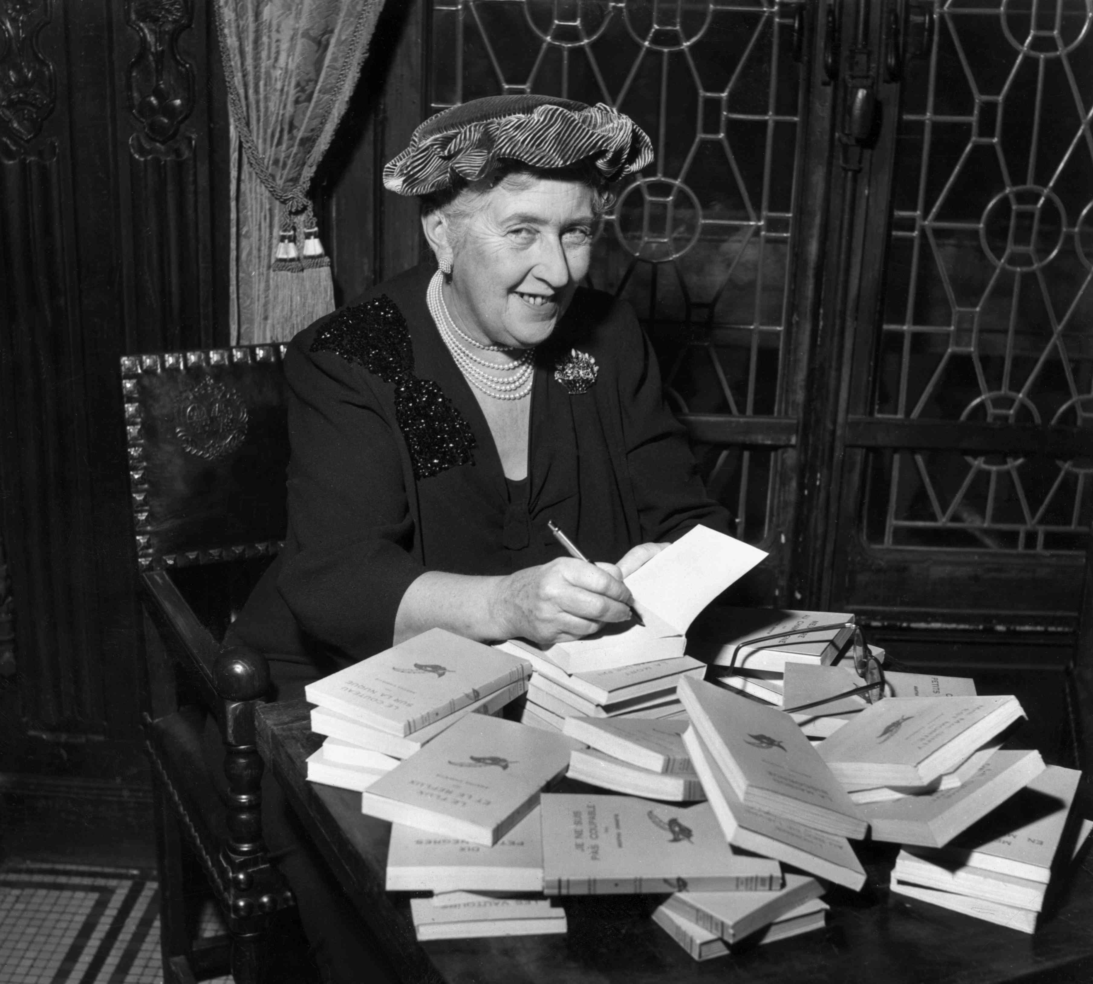 Agatha Christie signing a pile of books
