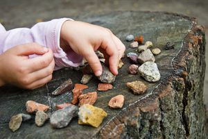 A child playing with many diverse stones and rocks on a tree stump