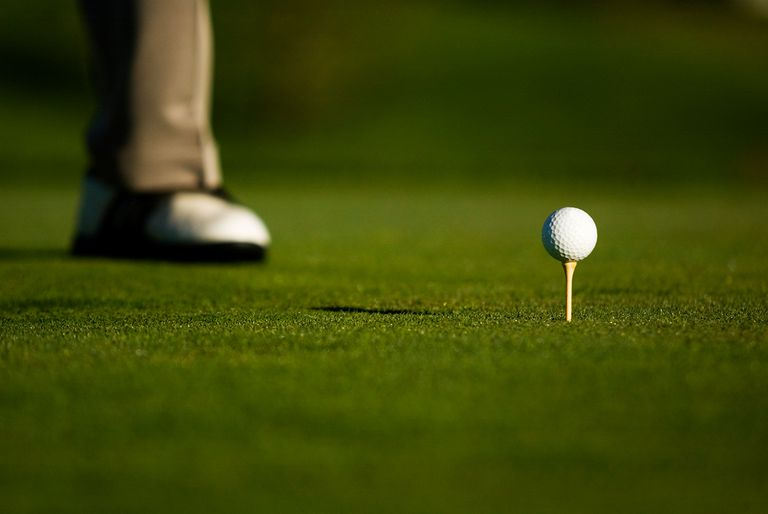 Golf ball on a tee with the foot of a male golfer in the background.