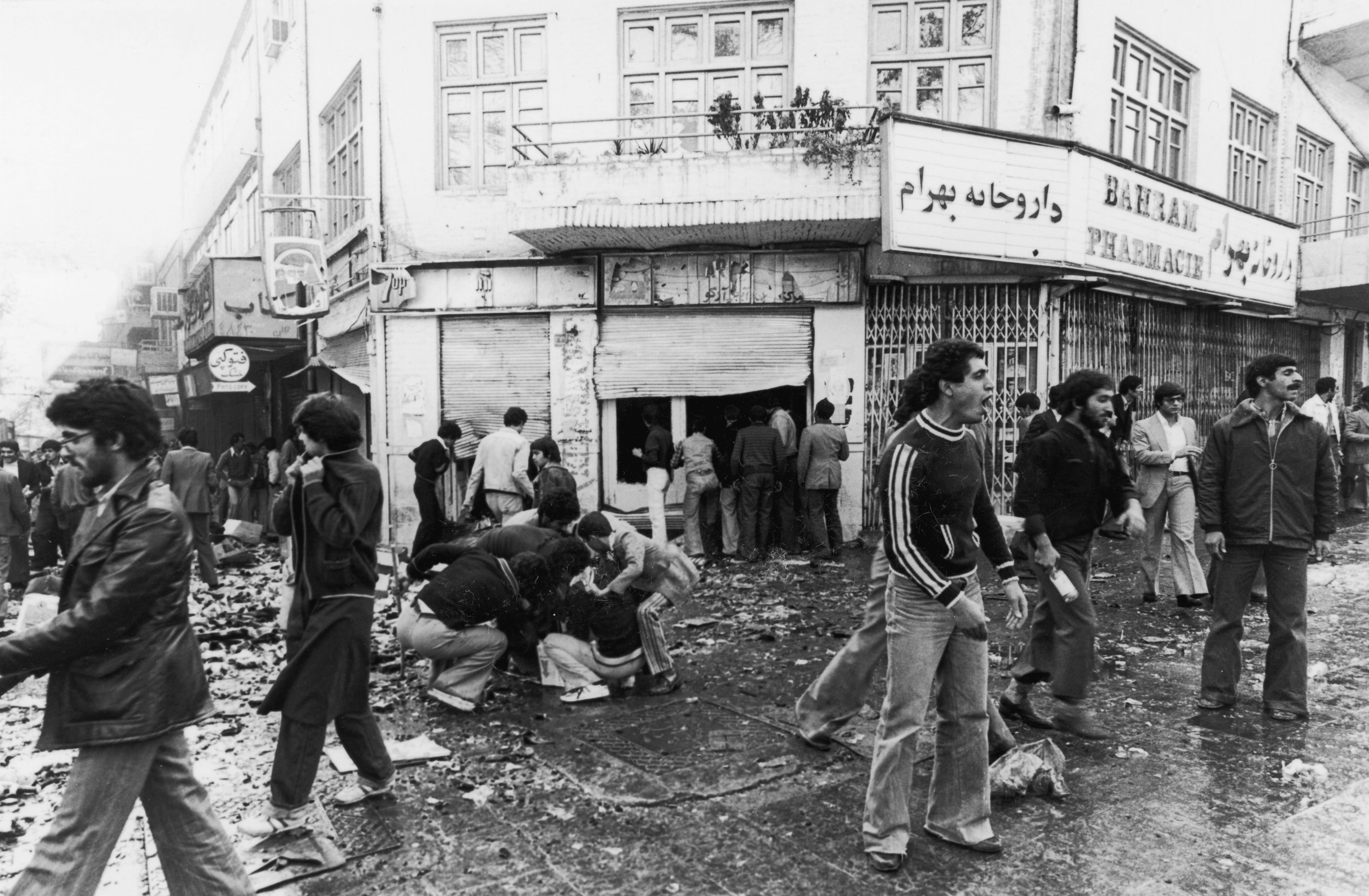4th November 1978 People gather around a casualty while others loot a shop after a riot in Tehran