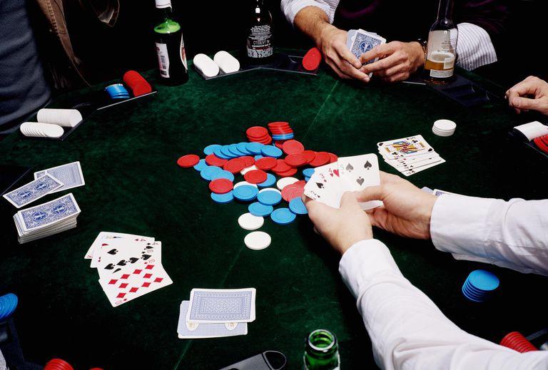 Four men playing poker, close-up
