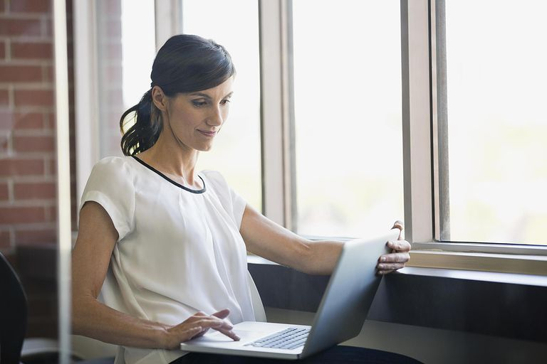 Businesswoman using laptop by window in office