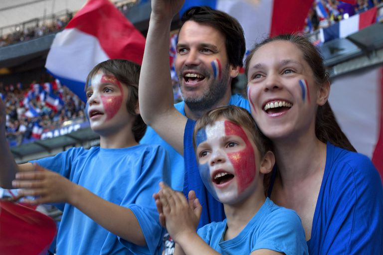 Patriotic French people with French flag colors painted on their faces