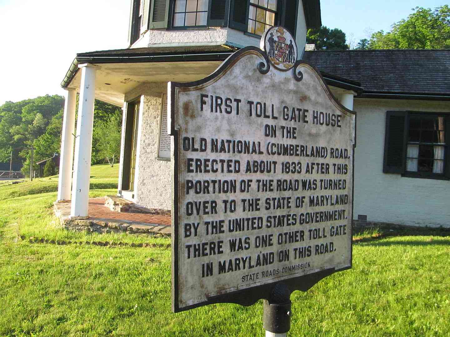 Toll house and historic marker on the National Road on a sunny day.