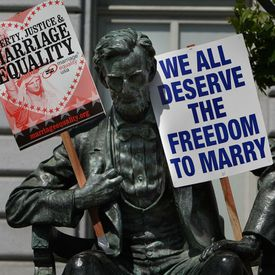 Abe Lincoln holding marriage signs