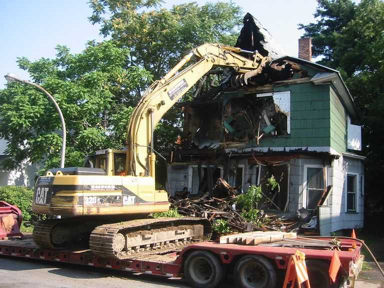 A tractor tearing down a house.