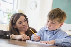 Female teacher and schoolboy in classroom
