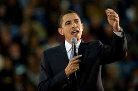 Barack Obama holding a microphone and giving a speech.